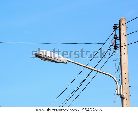 old three-phase power electricity line installed on top of a pylon with ceramic isolators blue sky background with a vintage style street lamp - stock photo