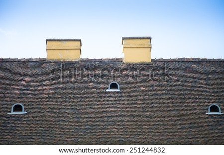 Old tiled roof with chimneys and dormers on blue sky background. - stock photo