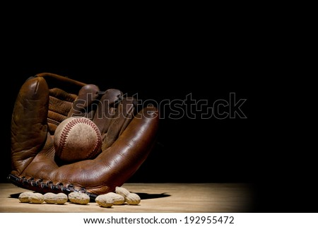 old time glove and baseball in spotlight with a few peanuts - stock photo