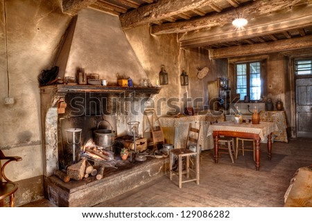 old times farmhouse - interior of an old country house with fireplace and kitchen - stock photo