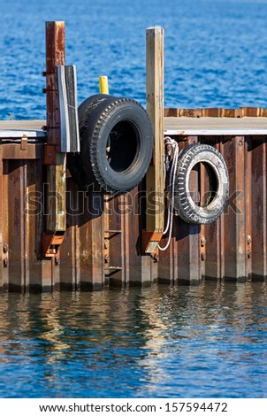 Old tires serve as boat bumpers on a rusty metal dock on the Great Lakes. - stock photo