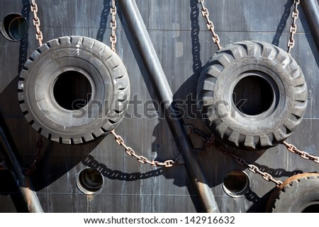 old tires used for protection of ship in the harbour - stock photo