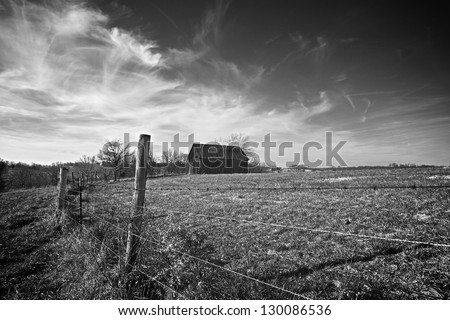 Old tobacco barn sits along barbed wire fence. - stock photo