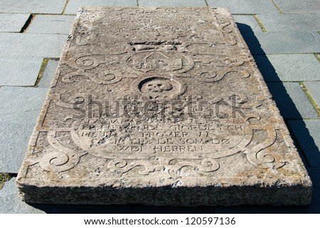 Old tombstone with skull and inscription - stock photo