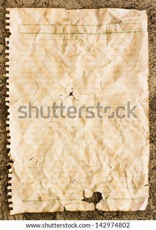 Old torn crumpled paper sheet on black floor - stock photo