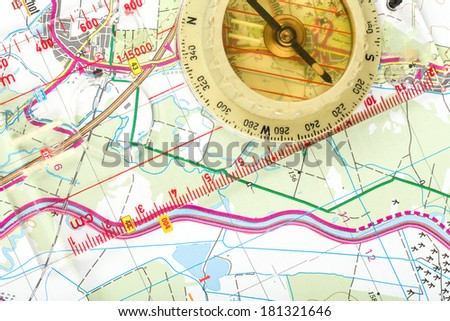 old touristic handheld compass on detailed territory map  - stock photo