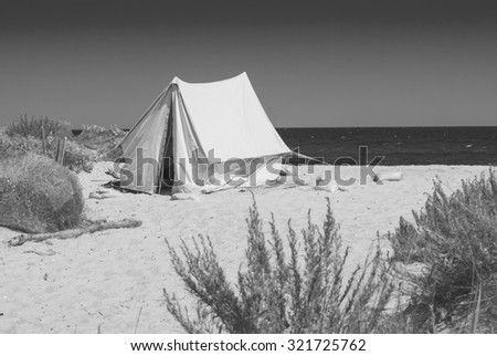 Old touristic tent on a beach of Black sea. Monochrome colors - stock photo