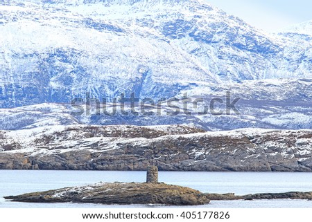 Old tower and Frozen mountains near the Arctic Circle from a ship  Norway