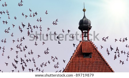 old tower with bell and many flying birds - stock photo