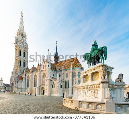 Old town architecture of Budapest. Buda temple church of Matthias. Buda's Castle District. Blue cloudy sky in background statue in foreground. Hungary, Europe.
