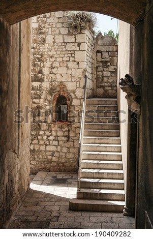 Old town passage with stairs and small wall shrine in historic center of Sibenik, Croatia - stock photo