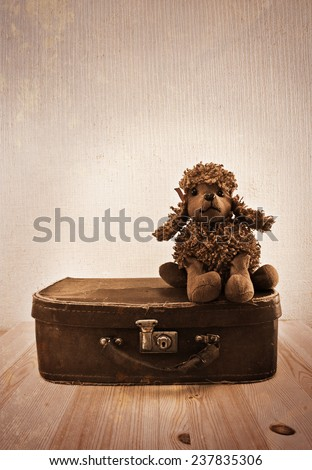 Old toy on a small road suitcase. Sepia toning. Imitation of old postcards - stock photo