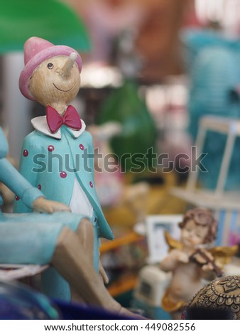 Old toys, including Pinocchio dolls, in a flea market in Italy - stock photo