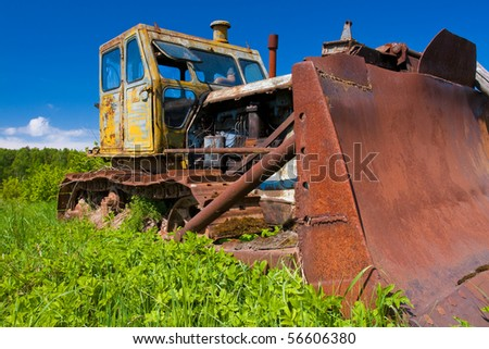 Old tractor in rural field - stock photo