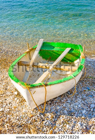Old traditional beautiful green fishing boat by the sea in Amorgos island in Greece - stock photo