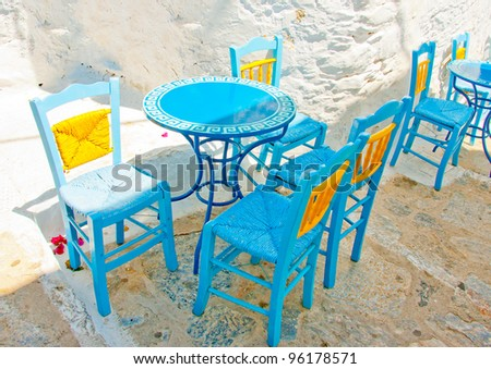 Old traditional beautiful iron made round shaped small coffee table and chairs out of a cafe in Chora the capital of Amorgos island in Greece - stock photo