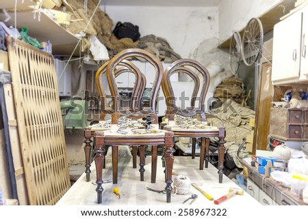 old traditional carpenter's workshop with armchairs repair - stock photo
