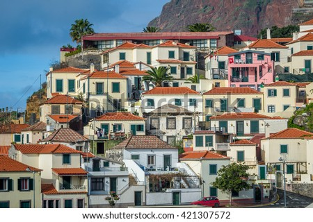 Old traditional colorful houses with red roofs in fishing village Camara de Lobos. South coast of Madeira island, Portugal.