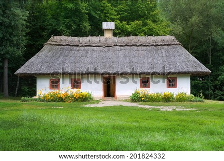 Old traditional cottage with thatch roof in national park. Ukraine - stock photo