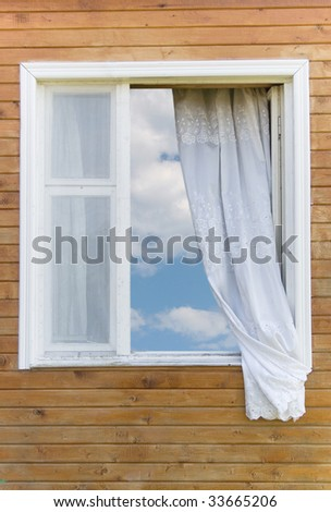 Old traditional country-style window in a wooden house (with the blue sky and white clouds in the window) - stock photo