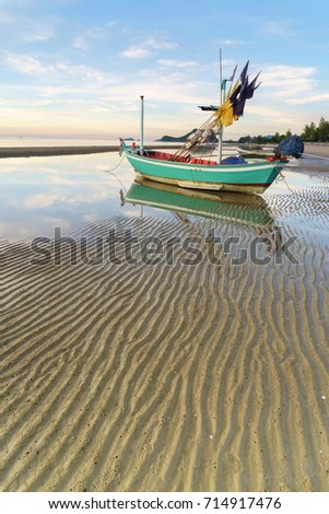 Old traditional fisherman boat on beach with its reflection in morning.