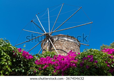 Old traditional windmill and bougainvillea in Kos island, Greece - stock photo
