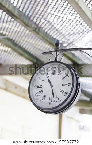 Old train station clock, detail of a classic watch for information - stock photo