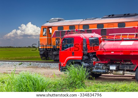 Old trains and fire trucks were moving on the road and rail which paddy cloudy sky as a backdrop. - stock photo