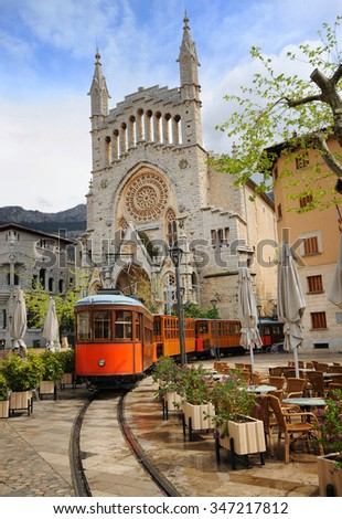 Old tram in the downtown of Soller in front of medieval gothic cathedral with huge rose window, Mallorca, Spain - stock photo