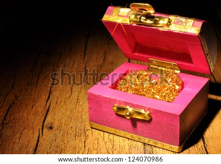 Old treasure chest with glowing gold - stock photo