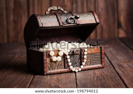 old treasure chest with pearl necklaces standing on wooden table - stock photo