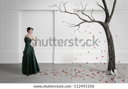 Old tree with falling leaves in a white room. Beautiful girl in front of the tree. A symbol of the fall. - stock photo