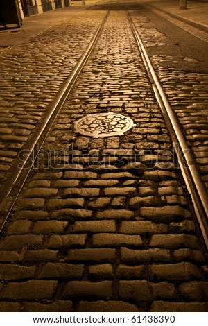 Old trolley tracks and cobblestones survive under the flaking asphalt pavement of this Brooklyn Heights street, Brooklyn, New York. A night time exposure.