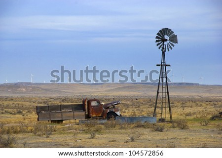 Old truck in an empty field next to an old-style windmill, with new turbine windmills in the distance on the horizon - stock photo