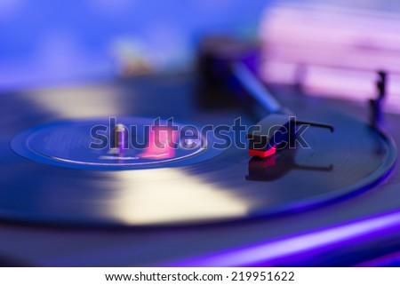 Old turntable with a record playing - stock photo