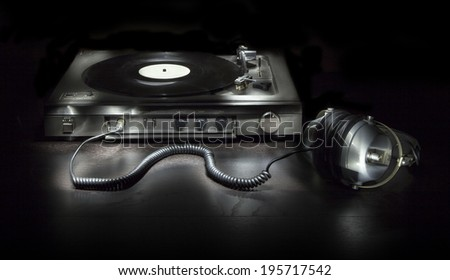 Old turntable with headphones isolated on a black background  - stock photo