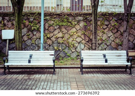 old two white bench in garden with stone background, process color  - stock photo
