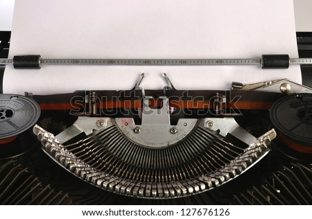 Old type writer with a blank sheet of paper. You can put your message on the paper - stock photo