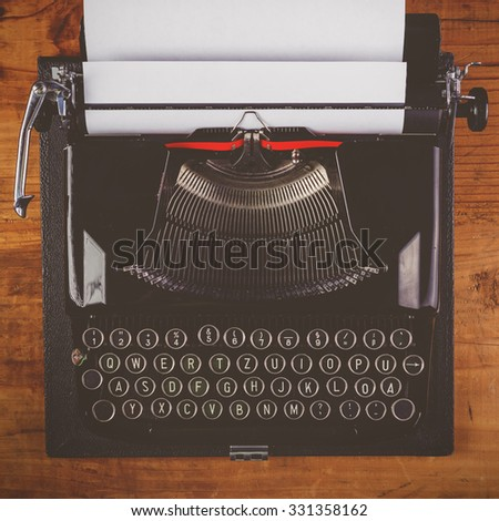 Old typewriter machine with paper top view retro toned image - stock photo