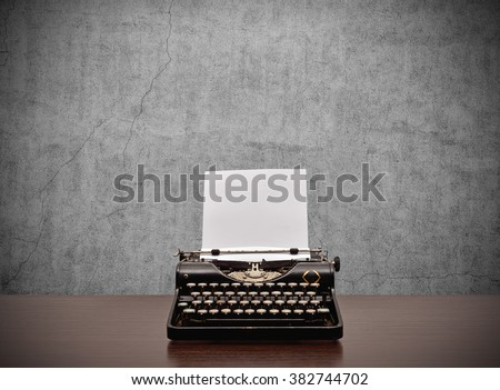 Old typewriter with blank paper on wooden table - stock photo
