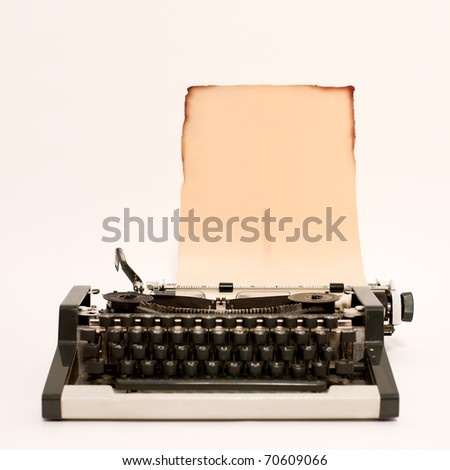Old typewriter with burned paper in it - stock photo