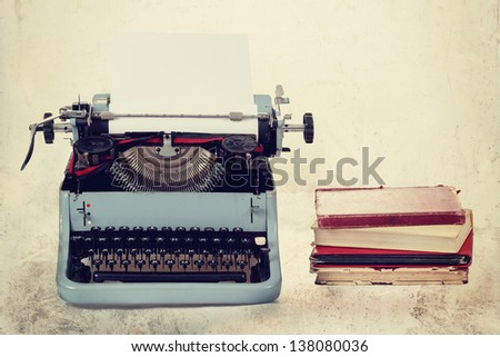 Old typewriter with paper and books, retro colors on the desk - stock photo