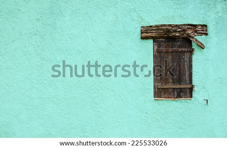 Old typical Mediterranean house with cyan stucco wall and closed wooden shutters. - stock photo