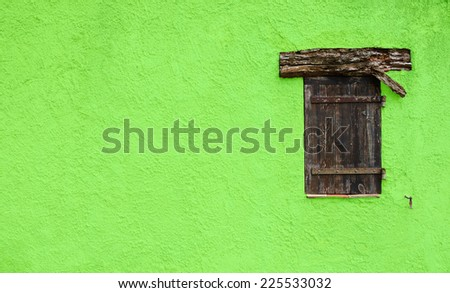 Old typical Mediterranean house with green stucco wall and closed wooden shutters. - stock photo