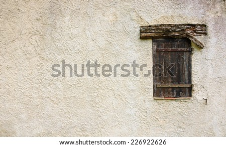 Old typical Mediterranean house with stucco wall and closed wooden shutters. - stock photo