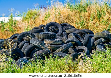 Old tyres polluting the nature - stock photo
