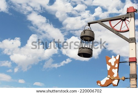 old unique western lamp post and boot in background blue sky with clouds, used as background  - stock photo