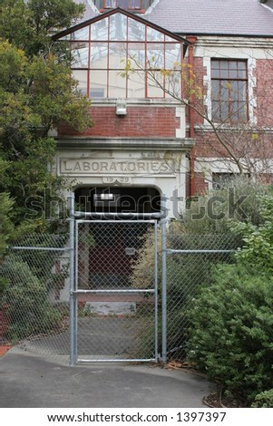 Old university laboratory entrance, built in 1929.  Currently disused due to earthquake risk. Security fence to keep people out. - stock photo