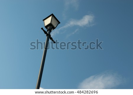 Old unlit streetlight with sky in the background