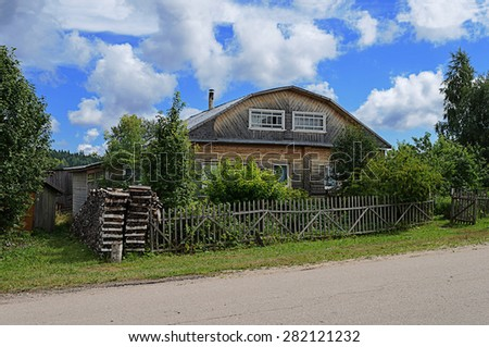 Old unpainted wooden house in russian village with a stack of firewood, summer time - stock photo